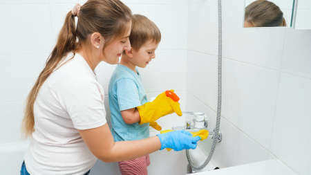 Smiling boy with mother washing bath and water sink. Children helping adults in housework and home cleanup. Stok Fotoğraf