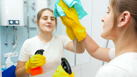 Smiling young woman cleaning and washing bathroom mirror with chemical detergent spray. Housewife doing home cleanup and housekeeping chores