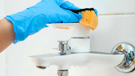 Closeup of hand in blue rubber glove washing and cleaning shiny metal water tap in bathroom while doing housework and cleanup at home Stok Fotoğraf