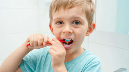 Portrait of little toddler boy looking in mirror while brushing teeth at morning. Child hygiene and healthcare