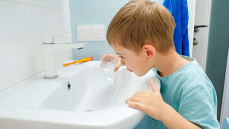 Portrait of smiling toddler boy rinsing mouth with water from glass after brushing and cleaning teeth with toothbrush and toothpaste. Concept of teeth hygiene and daily routine