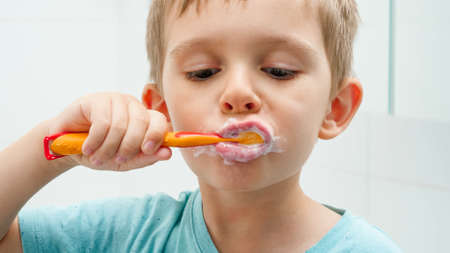 Portrait of funny toddler boy cleaning and brushing teeth at morning. Concept of teeth hygiene and child healthcare