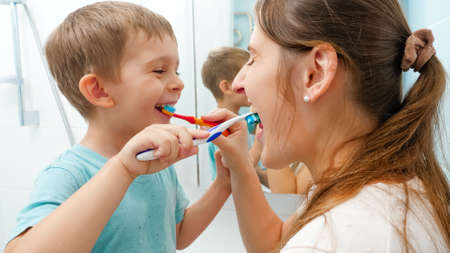 Smiling little boy with young mother brushing teeth and cleaning mouth with toothbrushes to each other. Family having fun while taking care of teeth hygiene and healthcare