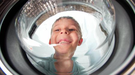 Funny smiling toddler boy looking inside drum of washing machine Stok Fotoğraf