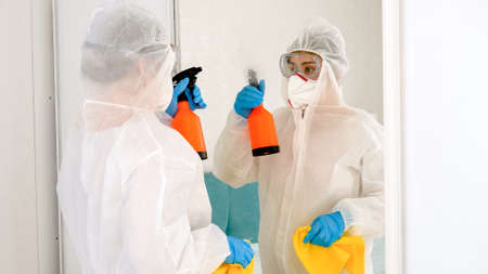 Person wearing protective biohazard suit desinfecting and cleaning house with chemical detergent Stok Fotoğraf