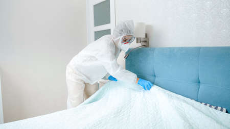 Hotel maid in protective medical suit and gloves tidying hotel room. Desinfection and hygiene during covid-19 and coronavirus pandemic