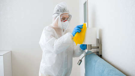 Housekeeper or maid cleaning and desinfecting furniture in hotel room. Person wearing protective medical suit doing cleanup at home Stok Fotoğraf