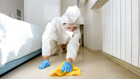Housewife wearing protective medical suit wasing and cleaning floor at home. Desinfection and hygiene during lockdown and staying at home at pandemic