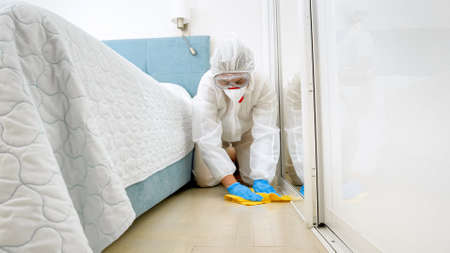 Housekeeper or maid in hotel wearing protective medical suit and mask washing and cleaning floor in room. Disinfection in hotels