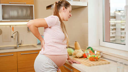 Young pregnant woman suffering from spinal pain holding hand on back and resting on kitchen after cooking and doing housework. Standard-Bild