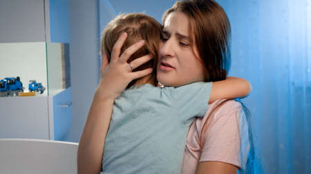 Portrait of young loving mother soothing and caressing scared little boy in children room at night. CHild being scared and crying of nightmare or bad dream