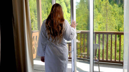 Beautiful young woman in bathrobe walking out of the hotel room on the balcony and looking on amazing pine forest and mountains. Stock fotó
