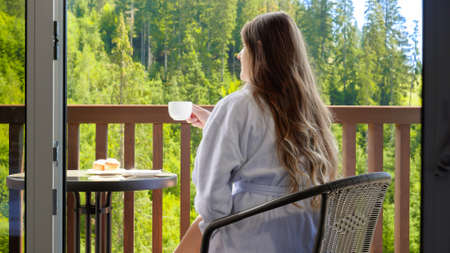 Beautiful brunette woman in bathrobe sitting on hotel room terrace and having breakfast. Concept of tourism and vacation in mountains at summer