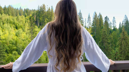 Beautiful young woman in bathrobe standing on hotel terrace or balcony and looking on the pine forest and mountains. Concept of tourism and vacation in mountains at summer