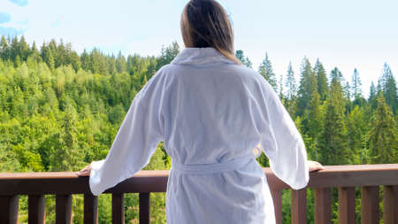 Beautiful young woman waking in the morning walking on hotel room terrace and having breakfast at morning. Concept of tourism and vacation in mountains at summer Stock fotó
