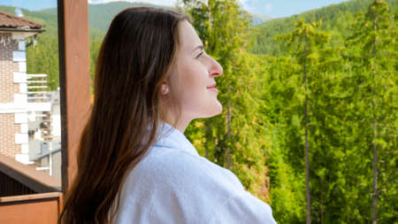 Portrait of beautiful smiling woman in bathrobe enjoying view on the mountains and forest from her hotel room. Concept of tourism and vacation in mountains at summer Stock fotó