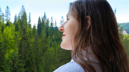 Young relaxed woman in bathrobe standing on hotel room balcony and looking on mountains and forest. Concept of tourism and vacation in mountains at summer