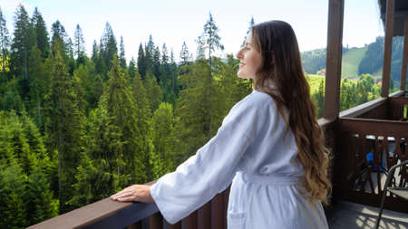 Portrait of smiling woman in bathrobe enjoying view on mountains from her hotel room. Concept of tourism and vacation in mountains at summer Stock fotó