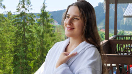 Happy smiling woman in bathrobe standing on hotel terrace and looking on the high mountains. Concept of tourism and vacation in mountains at summer