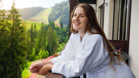 Beautiful smiling young woman in bathrobe looking on mountains and forest from the hotel room balcony Stock fotó