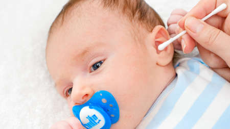 Closeup of cleaning newborn baby ears with cotton swab from ear wax. Concept of babies and newborn hygiene and healthcare. Caring parents with little children.