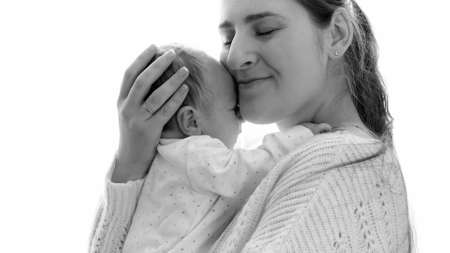 Black and white portrait of happy young mother hugging her little baby son against big window