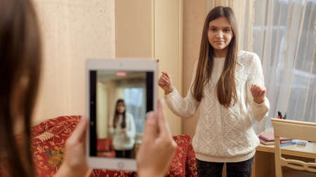 SMiling teenage girl dancing in front of smartphone recording video for posting in internet. Modern communication, social media and gadgets