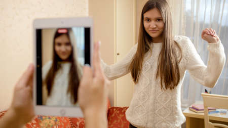 Recording video on tablet or smartphone of teenage girl dancing for posting in internet. Modern communication, social media and gadgets Stockfoto