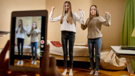 REcording video on smartphone of two teenage girls dancing for posting in internet. Modern communication, social media and gadgets
