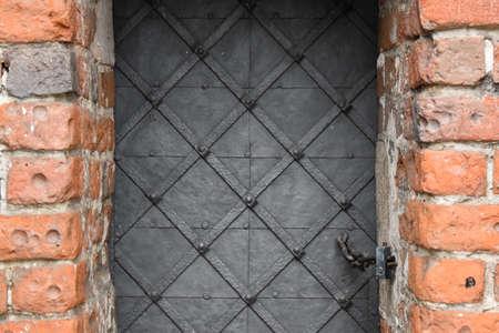 Metal door on a brick wall.