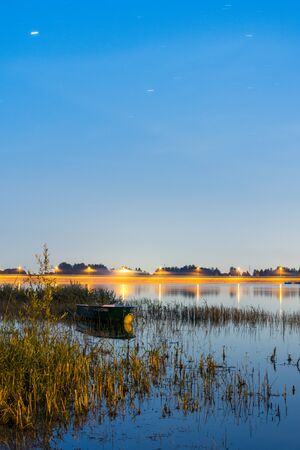 Illuminated rowboat at a lake at night