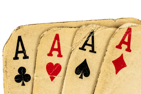 Four old dirty aces poker cards on a white background