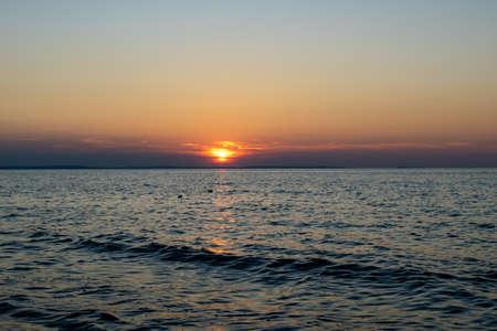 the setting sun against the backdrop of a calm sea Standard-Bild