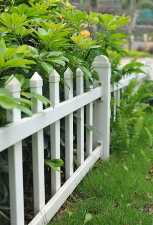 White picket fence and flower bed photo