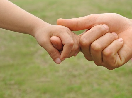 A child's hand holding an adult's finger Stock Photo
