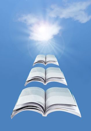 Flying open books over a blue sky Stock Photo