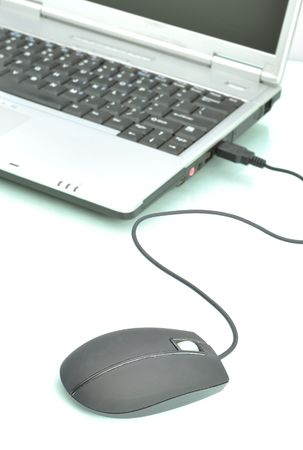 Laptop computer and a mouse against white background photo
