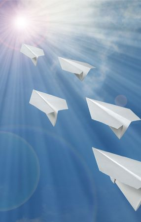 paper airplane in front of blue sky Stock Photo