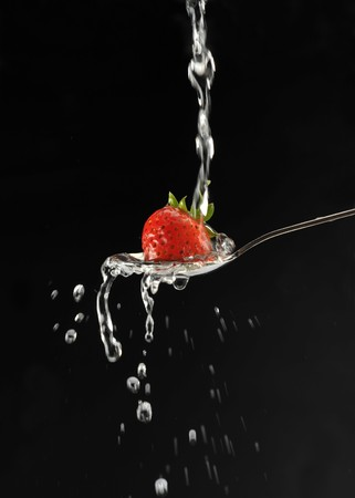 Strawberry in a spoon against a black background photo