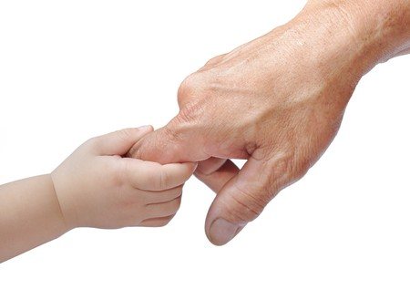 A childs hand holding an adults finger Stock Photo