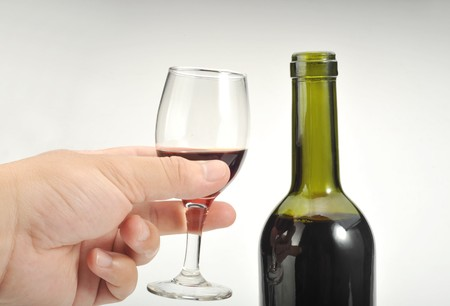 A glass of red wine in the hand photo