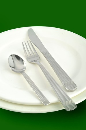 Knife, fork, spoon, and plates in green background