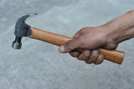 Hand holding old hammer
