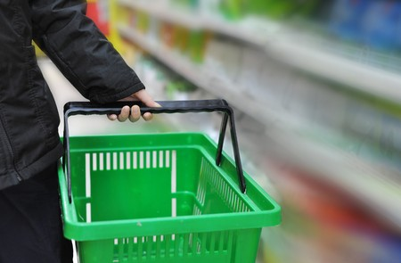 grocery baskets: hand is taking the shopping basket in the market Stock Photo
