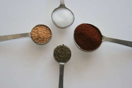 Spices in measuring spoons arranged in a circle photo