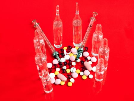 ampoules: Multi-coloured tablets, syringes and ampoules on a red background Stock Photo