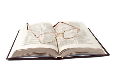 diccionarios: libro con gafas, sobre un fondo blanco