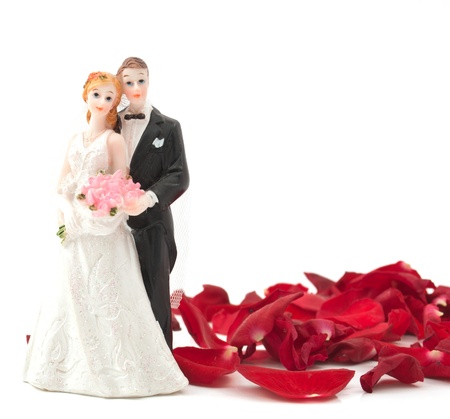 figurines: bride and groom with rose petals on white background