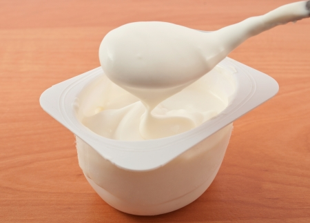 eating yogurt: Yogurt on a wooden table Stock Photo