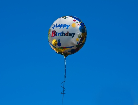 Balloon with Happy Birthday on the background of blue sky photo